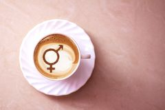 Symbol of gender equality. On milk foam coffee cups cappuccino stock images