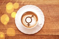 Symbol of gender equality. On milk foam coffee cups cappuccino royalty free stock photos