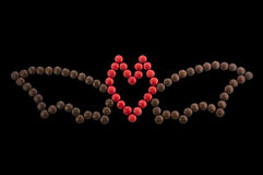 Symbol Halloween - a bat out of round candies isolated. On a black background. Body in the form of heart Royalty Free Stock Image