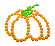 Symbol Halloween - a pumpkin. Composed of small round candies. Isolated on a white background Royalty Free Stock Photo