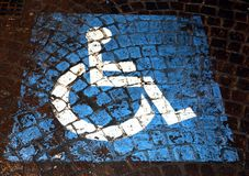 Symbol of handicapped parking painted on porphyry in the street Stock Photography
