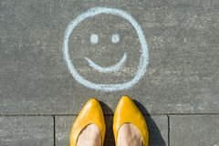 Symbol of happy smiley drawn on the asphalt and woman feet.  Stock Image