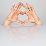 Symbol heart. Two hands placed in the shape of heart Stock Photos