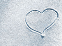 Symbol of heart on the background of fresh snow texture in blue tone. Royalty Free Stock Photos