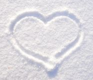 Symbol of heart on the background of fresh snow texture. Merry Christmas or Valentine`s Day Concept. Copy space for your stock photography