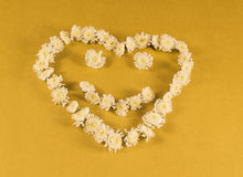 symbol of the heart from flowers, yellow background Royalty Free Stock Images