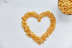 Cornflakes in a metal bowl on a painted white wooden background. The symbol of the heart is laid out of cornflakes. Royalty Free Stock Photography