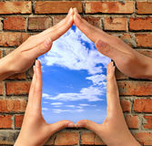 Symbol home. Home symbol made from hands over a brick with a window into blue sky conceptual photo illustration Royalty Free Stock Photos