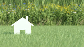 Symbol of house on grass field Stock Photo