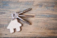 Key with house icon on wooden background Royalty Free Stock Images