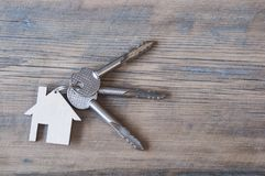Key with house icon on wooden background Royalty Free Stock Photography