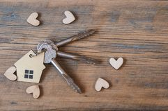 Key with house icon on wooden background Stock Photos