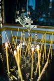 Symbol i ramen i kyrkan bredvid stearinljusen arkivfoto