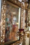 Symbol i ramen i kyrkan bredvid stearinljusen arkivbilder