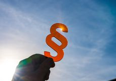 Symbol of Law and Justice - Paragraph / section sign. Holding in fingers at the sun royalty free stock images