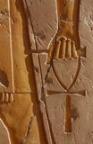 Symbol of Life. An ankh, an ancient Egyptian symbol of life, in hand of a god, on the wall of the mortuary temple of Queen Hapshepsut at Deir el-Bahri on the Royalty Free Stock Photo