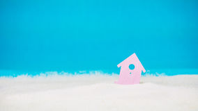Symbol of little lilac house on the sand with bright blue background Royalty Free Stock Photos