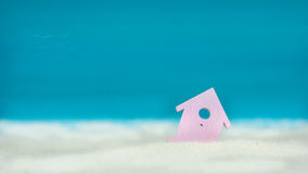 Symbol of little lilac house on the sand with bright blue painted sky background Stock Images