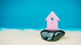 Symbol of little lilac house secured builed on black stone on blue background Stock Images