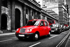 Symbol of London, the UK. Taxi cab known as hackney carriage. Black and white with red. Iconic English transportation, red buses in the background royalty free stock images
