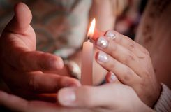 Four hands of young people protecting fragile candle light fire as a metaphor of care and protection during religious ceremony royalty free stock images
