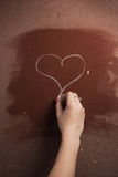 Symbol of love - heart drawn on the whiteboard,. Woman's hand drawing on the blackboard with chalk Stock Photography
