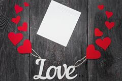Symbol of love and holiday of lovers. White lettering Lov with red hearts in rustic style.