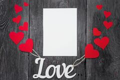 White letters Love with ropes and with red hearts, like balloons. space for text on a white sheet of paper
