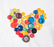 A symbol of love. The symbolic heart is composed of bright colored buttons on white background Stock Photo