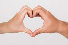 Symbol of love. Young dates hands making heart in isolation Royalty Free Stock Photo