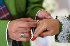 Malay wedding ceremony. Malaysia. Groom putting a diamond ring to his bride's finger Royalty Free Stock Photo