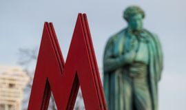 The symbol M-metro. Against the background of Pushkin monument Stock Photo