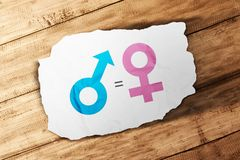 Symbol of male gender is equal to female in white paper on wooden table. Equality gender concept stock photography