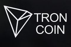 Symbol of new cryptocurrency - Tron Coin on black grunge background. Symbol of new cryptocurrency - Tron Coin on the black grunge background stock images