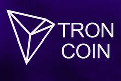 Symbol of new cryptocurrency - Tron Coin on ultra violet background. Symbol of new cryptocurrency - Tron Coin on the grunge ultra violet background royalty free stock image
