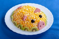 Symbol of the new 2019. Salad in the form of a cute pig on a blue background. Corn salad in the style of the New year - the year of the yellow pig. Symbol of the stock photography
