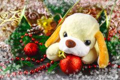 Symbol of the 2018 new year toy dog surrounded by decorative Christmas elements and fir branches. Symbol of the 2018 new year toy dog surrounded by decorative royalty free stock image