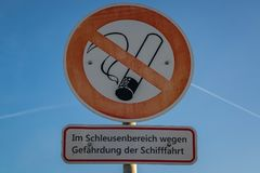 Symbol: No smoking. Text: In sluice area, because of danger for. Shipping German, seen in Duisburg, North Rhine-Westphalia, Germany Stock Photography
