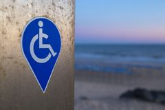 Symbol for people with disability adapted devices. Sunset backgroun at beach stock photography