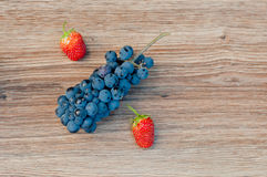 Symbol percent made of grapes and strawberries on wooden background Stock Images