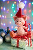 Symbol 2019 pink pig sitting on a gift with candy cane on background with illumination stock photo