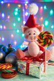 Symbol 2019 pink pig sitting on a gift with lollipop on background with illumination royalty free stock photography