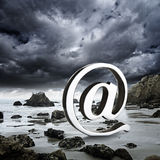 At symbol on a rocky beach Royalty Free Stock Images