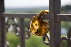 Symbol romance love padlock shape heart bridge sunny day closeup. Golden lock attached fence summer shallow depth of field close up Royalty Free Stock Photography
