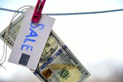Symbol of sale dollar hanging on a rope with a pinch 100 Stock Photo