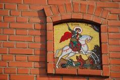 Symbol som visar St George det segerrikt på en tegelstenvägg Arkivfoto