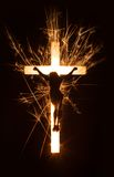 Symbol of sparkly Jesus on cross on dark background. Stock Photos
