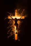 Symbol of sparkly Jesus on cross on dark background. Stock Photos
