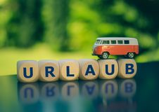 Symbol for summer holidays. Cubes form the German word `Urlaub` `vacation` in English. A miniature van is placed on the cubes stock photography