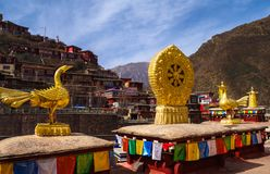 Symbol of Tibetan Buddhism. Golden wheel , golden peacock , symbols on the top of a Tibetan Buddhist temple Stock Photos